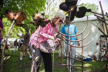 Riverside resident Nancy Smith inspects the whimsical copper artwork at the tent of Nebraska artisan Adam Weiss during Riverside Arts Weekend on May 18 in Guthrie Park in downtown Riverside. | Alexa Rogals/Staff Photographer