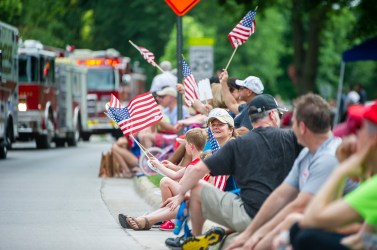 Folks line the curb in Riverside, waving flags as public safety vehicles pass by during the Fourth of July parade last week. (ALEXA ROGALS/Staff Photographer)