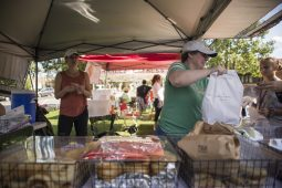 Customers purchase bagels from The Daly Bagel on Wednesday, Aug. 28, during the Riverside Farmers Market near the water tower in downtown Riverside. (ALEXA ROGALS/Staff Photographer)