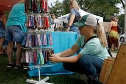 Marsha Shipley, of La Grange Park, looks at keychains available at a booth at the Brookfield Fine Arts Festival on Saturday, Sept. 21.