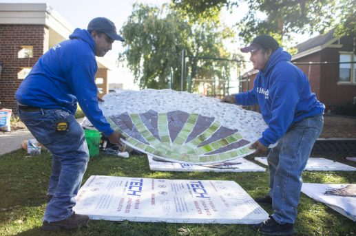 Volunteers carry pieces of the mural to be attached to the wall at Hollywood Elementary School on Saturday, Oct. 19. (ALEX ROGALS/Staff Photographer)