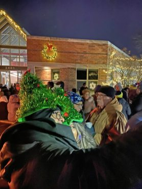 Wearing holiday-inspired headgear, two women snap a selfie next to the fire pits in front of the North Riverside Village Commons during the tree-lighting ceremony on Dec. 4. (Bob Uphues/Editor)