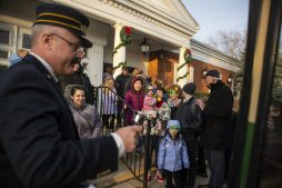 Brookfield trustee and sometime holiday trolley conductor Brian Conroy, left, rings a bell as guests get on board to travel to other sites in the village on Dec. 7 during the annual holiday celebration in Brookfield.|