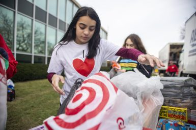 Natalie Barragan, a student in Jessica Mauritzen's Spanish 2 class at RBHS, grabs a bag of toys to deliver to the WGN Morning News' annual toy drive on Dec. 13 in Chicago. The class raised about 500 items after their week-long effort. | ALEX ROGALS/Staff Photographer