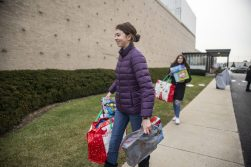 RBHS freshman Josie Randall, of Riverside, carries bags of gift donations to the donation tables on Dec. 13, during a toy drive at the WGN Studios in Chicago. | ALEX ROGALS/Staff Photographer