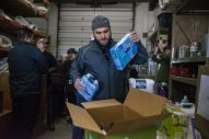 Adam Bolt, of Riverside, packs up coat and body wash for families in need on Dec. 22, at Twilight Party Rentals in Brookfield. | ALEX ROGALS/Staff Photographer