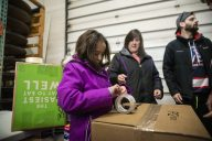 Isabella Buczek, 9, of North Riverside, packs up a box of food for a family in need on Dec. 22, at Twilight Party Rentals in Brookfield. | ALEX ROGALS/Staff Photographer