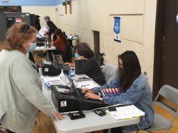Ema Bothwell, 16, a student at Lyons Township High School, checks in a voter at Congress Park School in Brookfield on Nov. 3 (BOB SKOLNIK/Contributing Reporter)