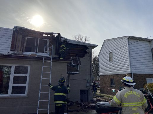 A Riverside firefighters takes down a section of face brick that detached from the wood structure underneath at the rear of the home. | Bob Uphues/Editor