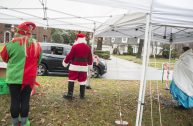 From left, Megan Siska, Ron Malchiodi and Elizabeth Nelson-Sifuentes, wave to motorists on Dec. 12, during a drive-by Santa event outside of Scout Cabin in Riverside.