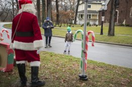 Families walk by Ron Malchiodi, Riverside parks and recreation director, dressed as Santa Claus and say hello on Dec. 12, during a drive-by Santa event outside of Scout Cabin in Riverside.