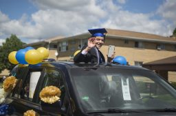 Komarek School eighth-graders wave from their vehicles to well-wishers lining a parade route from the school to Village Commons before a graduation ceremony at Veterans Park on May 30. (Alex Rogals/Staff Photographer)