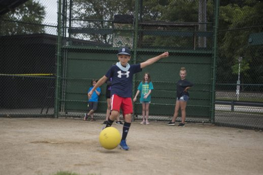 A camper goes up and kicks the ball on Aug. 3, during a game of kickball at Kiwanis Park. (Alex Rogals/Staff Photographer)