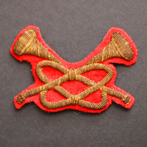 Photograph of a RCMP Trumpeter badge in gold wire with red felt background (Source of photo - Sheldon Boles)