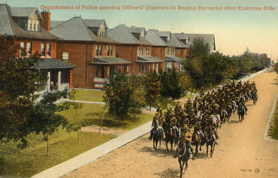 Photograph of RNWMP members riding past the officer's houses at Depot (Source of photo - Ric Hall's photo collection)