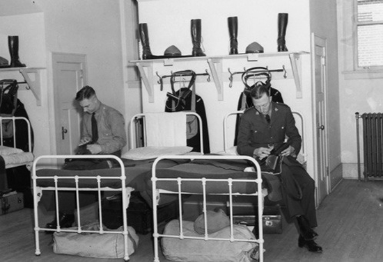 "1930 - Photograph of RCMP members sitting at their bed polishing their kit.  Photo taken in   ""B"" Block at Depot Division in Regina (Source of photo - Sheldon Boles)."