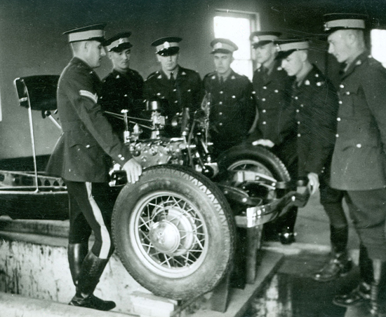 "Photograph of RCMP ""Depot"" recruits being taught about the fundamentals of police vehicle maintenance. (Source of photo - Ric Hall's Photo Collection)."