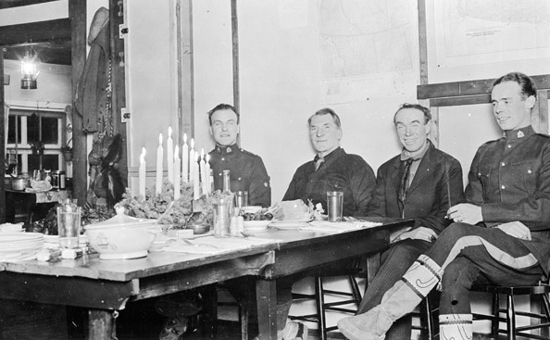 Photograph of early RCMP members celebrating Christmas at an unknown location.  No electric lights in these rooms (Source of photo - Ric Hall's Photo Collection).