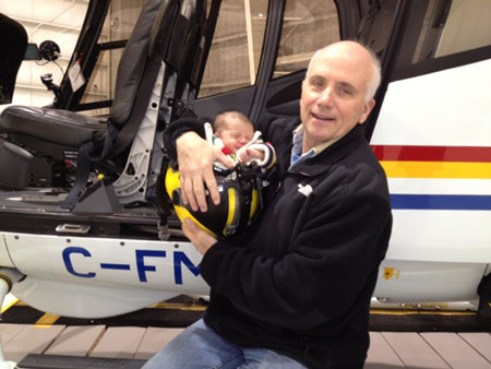 Photograph of RCMP Veteran Perry Edwards holding his young son (Ryder) inside a RCMP helicopter pilot's helmet (Source of photo - Ric Hall's Photo Collection).