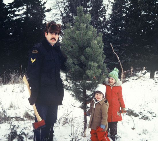 Photograph of Corporal Peter Bird with his two daughter retrieving a Christmas tree while being stationed at Atlin Lake Detachment (Source of photo - Ric Hall's Photo Collection).