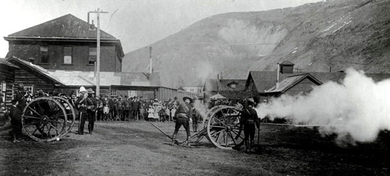 May 24, 1900 - Photograph of Victoria Day celebrations with the NWMP members firing a cannon at Fort Herchmer while Dawson residents looked on (Source of photo - Ric Hall's Photo Collection).