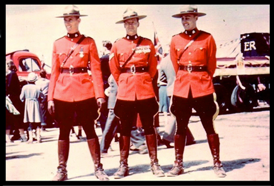 Photograph of three RCMP members in red serge.  Corpoal Bernie Parker is in the centre. (Source of photo - Ric Hall's Photo Collection).