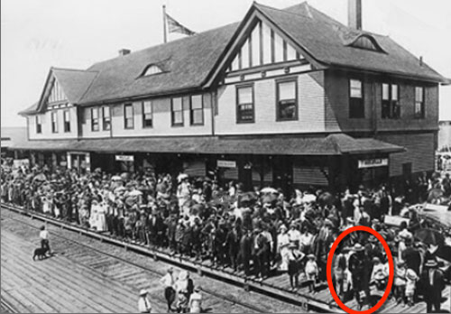 1939 - Photograph of the Melville Saskatchewan training station with crowds of people waiting for the arrive of the Royal Train containing King George VI and Queen Elizabeth. Cst. Tom Raisbeck is probably the member circled in red.