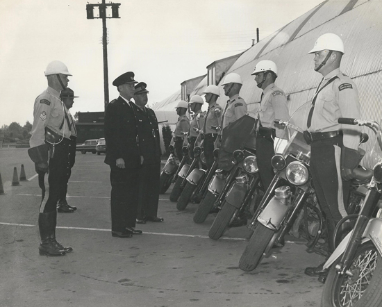 1963 - Cloverdale Fairgrounds in Surrey, BC:1963 motorcycle Course.  Supt Woods - Johnson  and Chief MACKIE  New West PD inspecting, with Sgt Mert ROWDEN i/c Traffic,   S/Sgt Wm MORRISON i/c Cloverdale Det.   In the picutre    Csts  Gord CAIRNY,  Wik HUGGANS New West PD, myself, Wayne HANKY. Can't see the other two and don't have a list.  Taken by the south wall of the Cloverdale Curling rink, just south of the Cloverdale Race Track.  Cpl. Bill Hulgaard and Cpl. Wm Todd were the instructors.  There were m/cs in Cloverdale, and Burnaby.  The training was required to be posted to the Pattullo Bridge Det. (Source of photo - Marv Ukraineitz)
