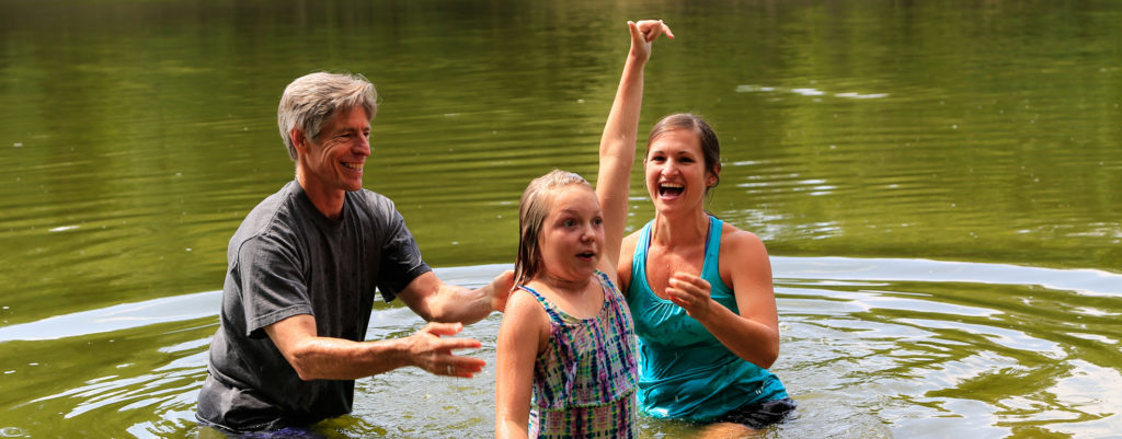 girl raising hand after being baptized