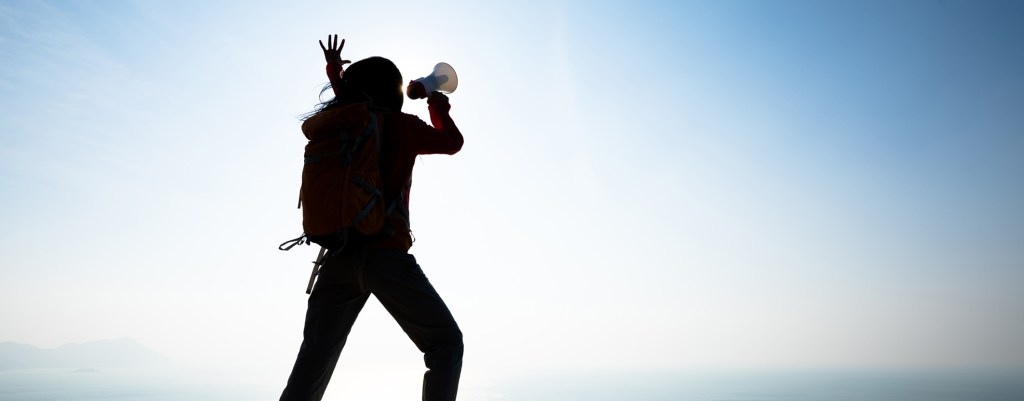 woman on top of mountain shouting through megaphone