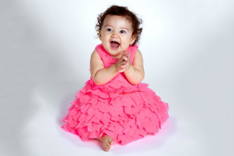 An adorable and happy baby girl sits on a white background clapping her hands and smiling with excitement. She is Native American and Hispanic.