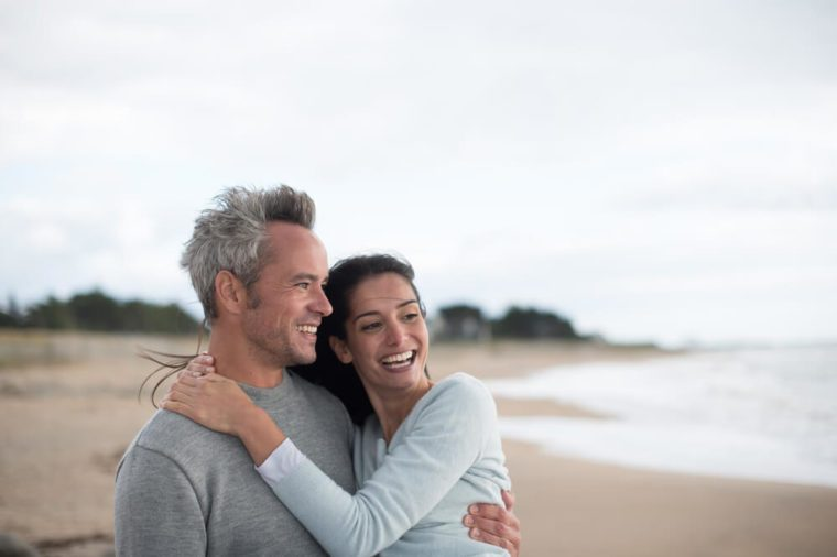 middle-aged couple are walking on the beach, they wear sweaters and jeans
