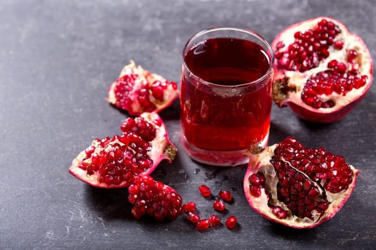 glass of pomegranate juice with fresh fruits on dark background.