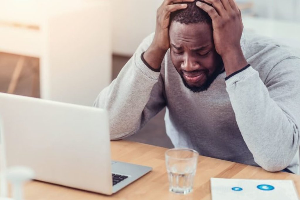Stressed African American guy crying at work