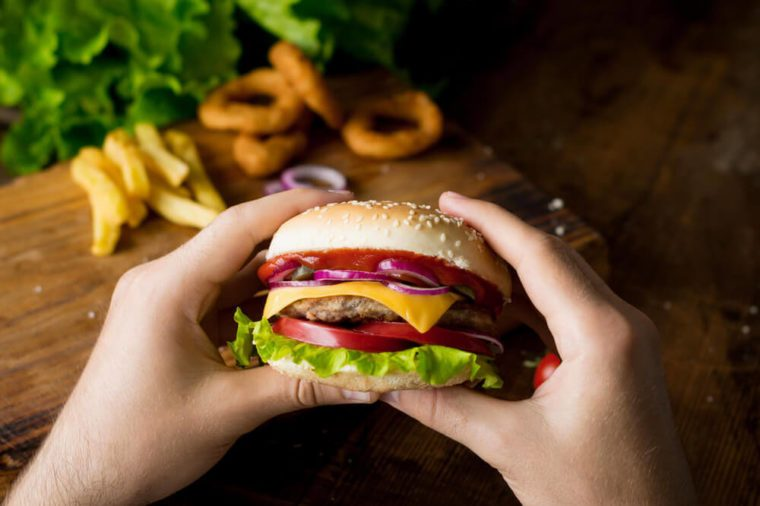 Cheeseburger. Man hands holding burger with cheese, red onion, tomatoes, lettuce green salad and pickles. Closeup view, selective focus