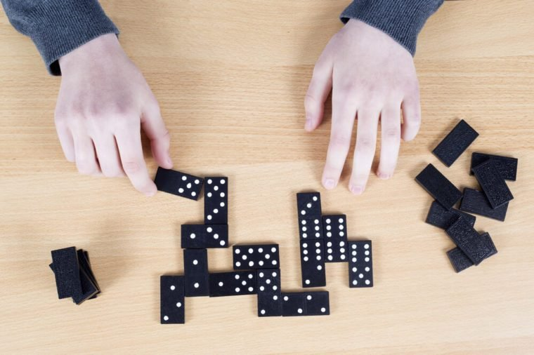Top View Of Female Hands And Black Dominoes On Wooden Board