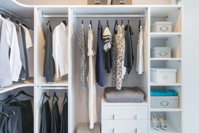clothes hanging on rail in white wardrobe with box and shoes