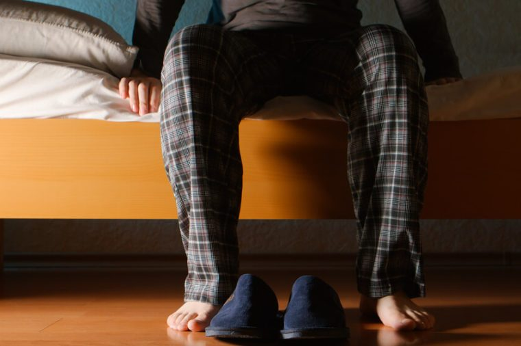 Man sits on a bed in the night at home
