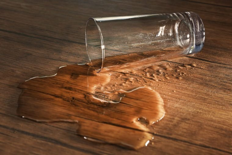 Glass of water spilled on wooden background
