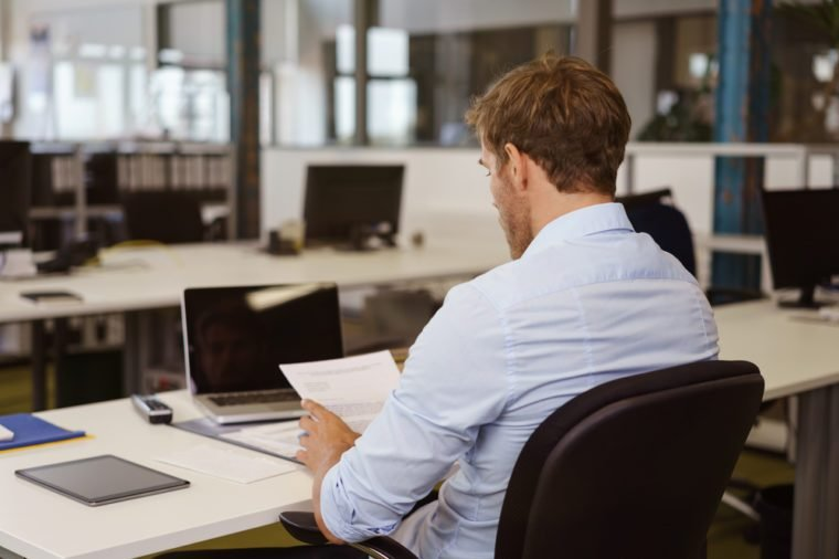 Businessman sitting at a table reading a document in a large open plan office, view from behind over his shoulder