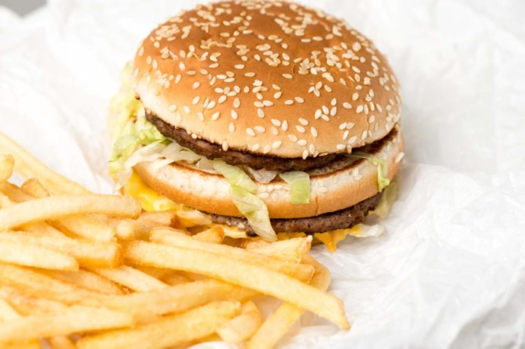 Double burger with french fries on white paper
