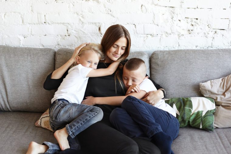 Portrait of happy young European female sitting on grey couch with two little sons who hugging her tight, feeling need of her love and support. Two male siblings sharing attention of their mother