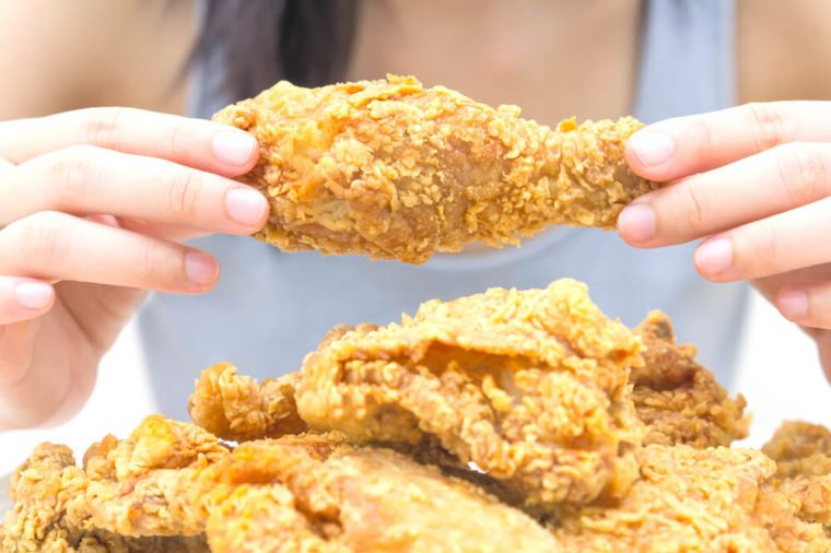 Woman holding and eatting fried chicken in white plate on white table