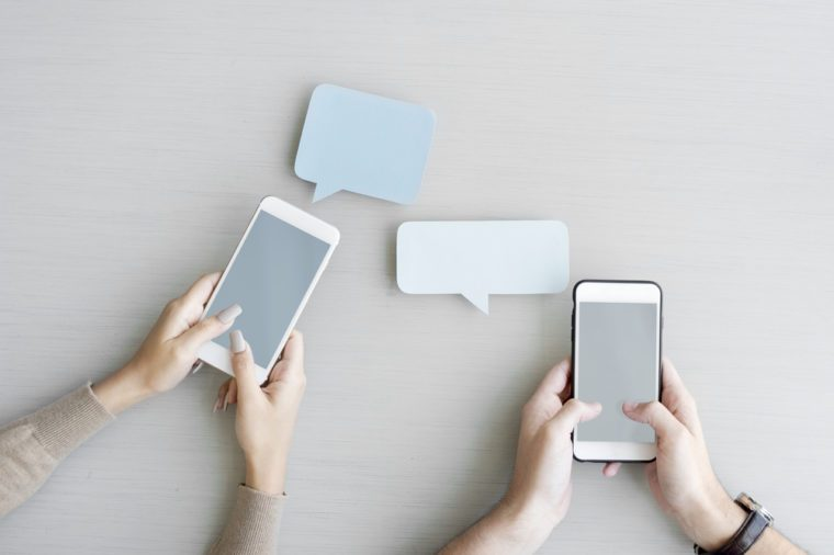 Hands Holding Mobile Phone with Blank Speech Bubble
