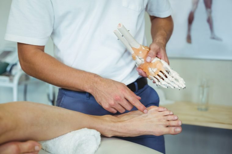 Physiotherapist explaining feet model to patient in clinic