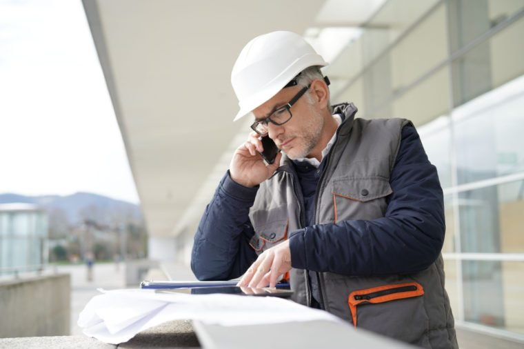 Engineer working on outdoor project and talking on phone