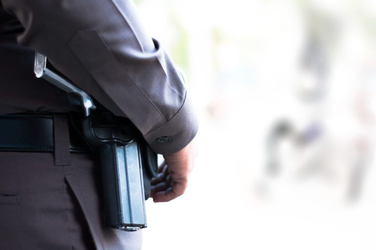 The side of policeman with gun.