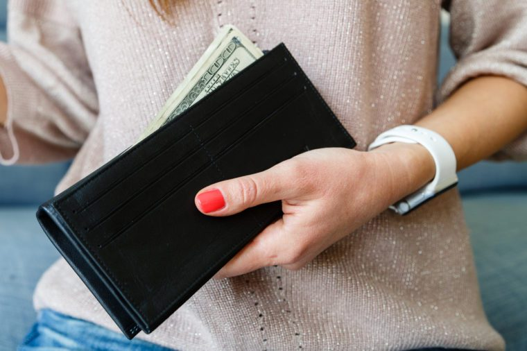 female hand close-up hold a black purse in which dollars lie