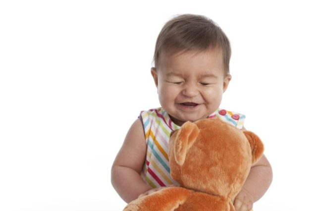 Baby girl having fun with her toy bear