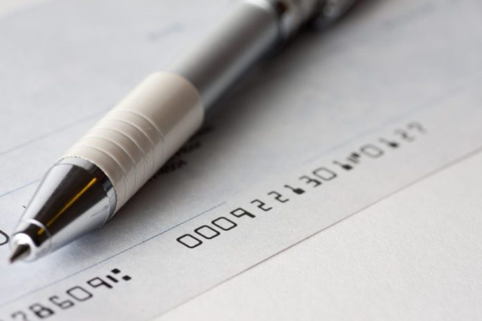 Close up shot of a cheque or cheque with a pen